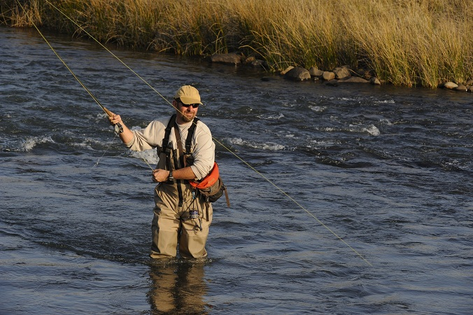 fly fisher wearing waders